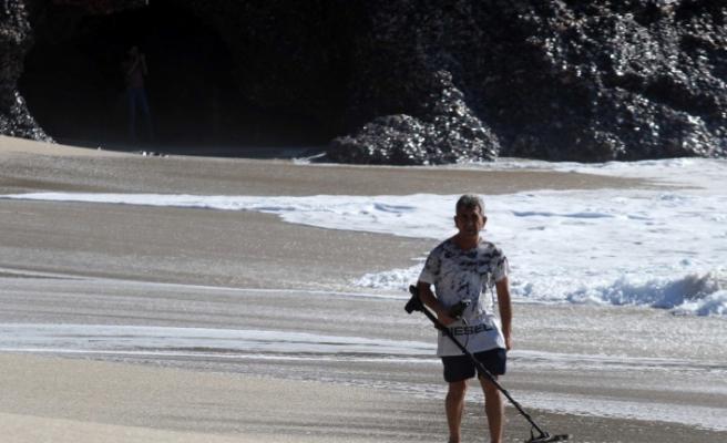 Define avcıları, dalgaların geri getirdiği turistlerin düşürdüğü altınları arıyor